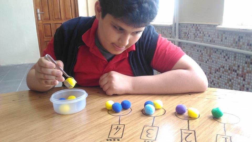L'élève critique les chiffres avec des bouffées à l'aide d'une pince.